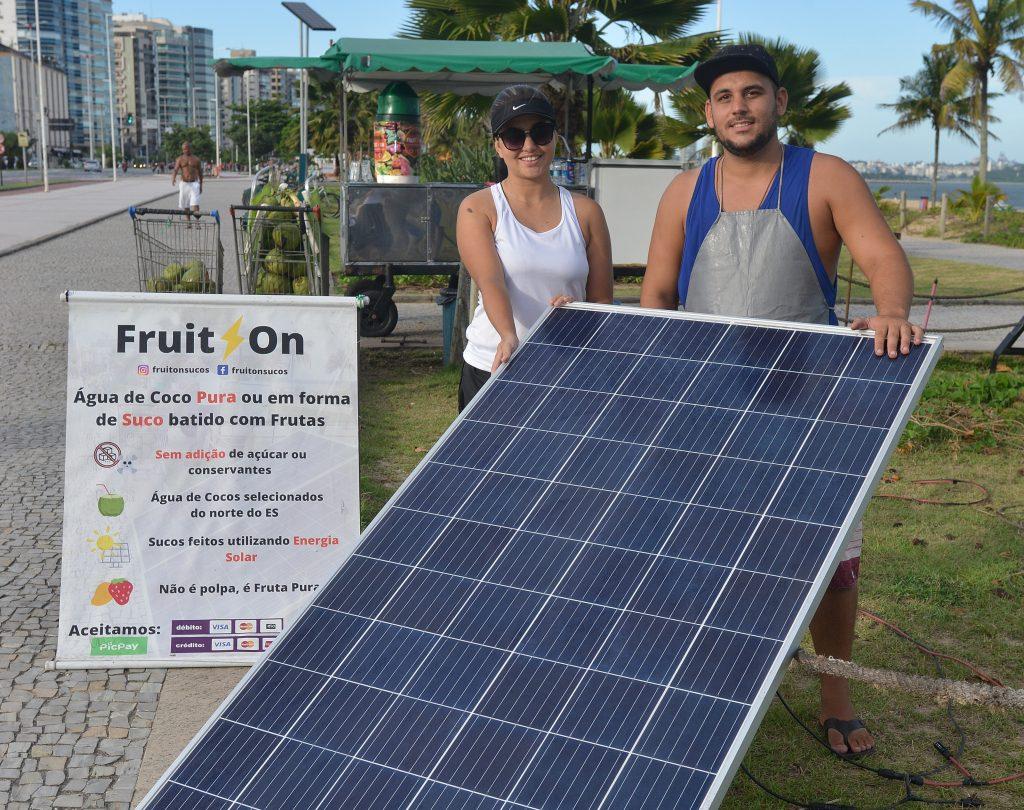 Simon e Juliana Belmok, vendedores de coco e suco na praia de Camburi, Vitória, que usam placa de energia solar para gerar energia. Foto: Chico Guedes